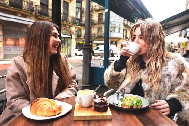 Twee vrienden ontbijten op een terras op een winterochtend in donostia-san sebastian baskenland.