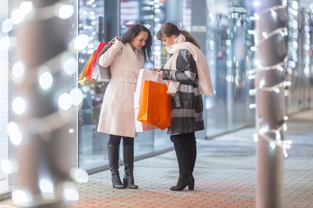 Twee vrienden ontmoeten elkaar voor een winkelcentrum en kijken naar cadeaus in hun tassen die ze voor kerstmis hebben gekocht.