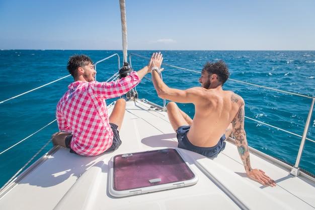 Twee vrienden op een boot zijn blij en doen high five, de dag is mooi, ze genieten van het leven