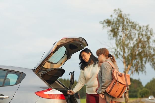 Twee vrienden pakken spullen in de auto die ze tijdens hun vakantie met de auto gaan reizen