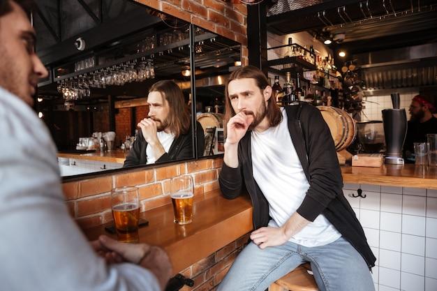 Twee vrienden praten in de bar
