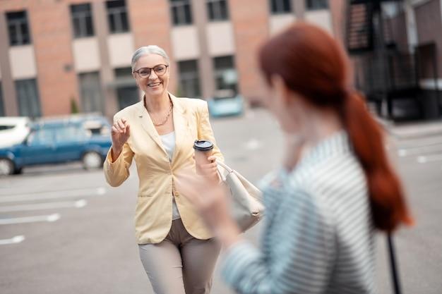 Twee vrienden. tevreden grijsharige blanke zakenvrouw met een papieren kopje koffie die naar haar vriend buiten loopt