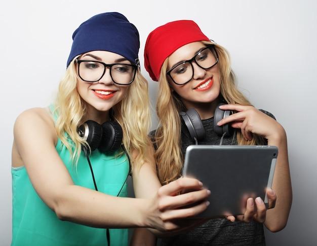 Twee vrienden van hipstermeisjes die selfie met digitale tablet nemen, studioschot over grijze vackground