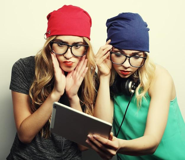 Twee vrienden van hipstermeisjes gebruiken digitale tablet, studio-opname over grijze vackground