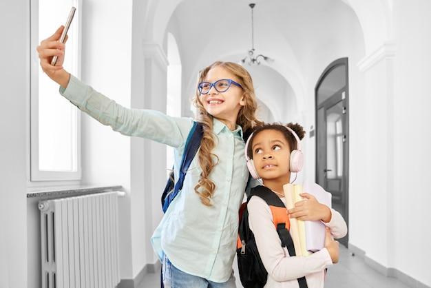 Twee vrienden van schoolmeisjes die foto nemen bij smartphone