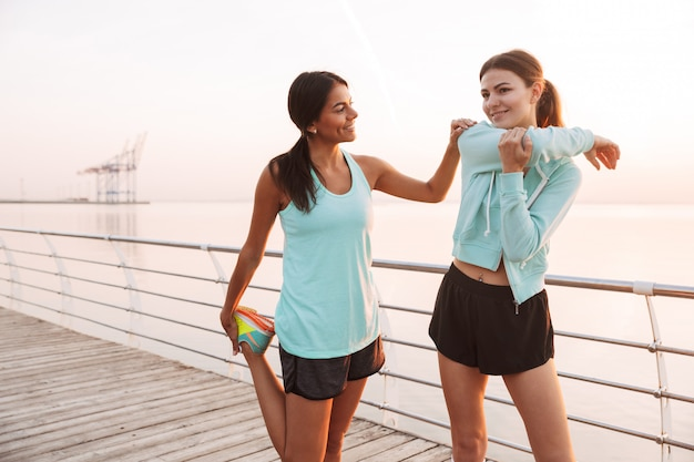 Twee vrienden van sportvrouwen in openlucht op het strand maken sportoefeningen