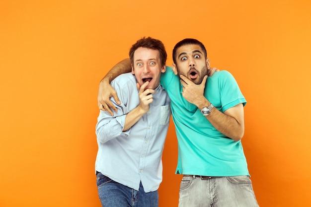 Twee vrienden van verbazing knuffelen zijn kin vasthoudend en kijken naar de camera met een geschokt gezicht