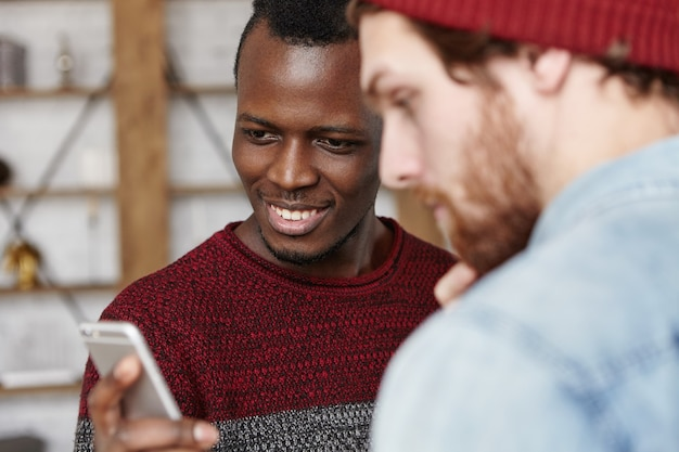 Twee vrienden van verschillende rassen hebben plezier binnenshuis, met behulp van elektronische gadgets