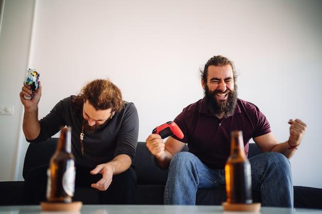 Twee vrienden vieren een overwinning op een gillend en poseren videogame