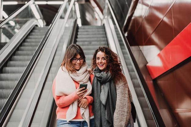 Twee vrienden wachten naar beneden gaan op het station alvorens een trein te halen. mobiele telefoon gebruiken. reisfotografie