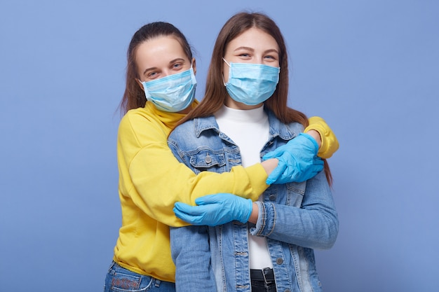 Twee vrienden zijn in een goed humeur, het dragen van medische maskers en handschoenen