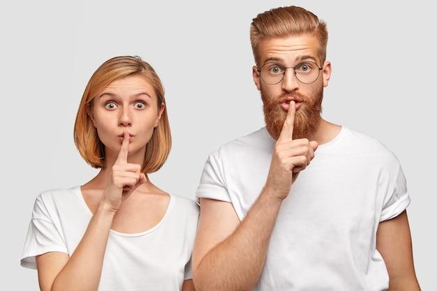 Twee vriendin en vriend maken een stil gebaar, vragen niets over hun geheim en zijn stil, hebben verrassende uitdrukkingen