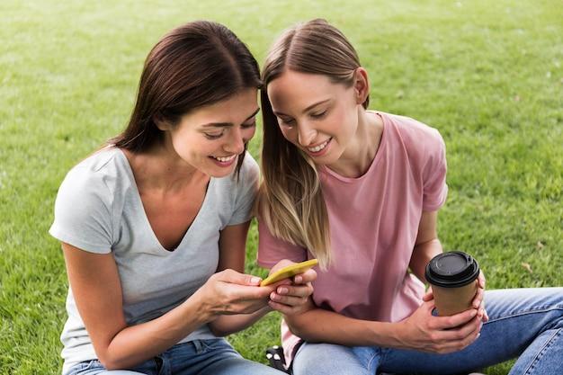 Twee vriendinnen buiten met smartphone en koffie