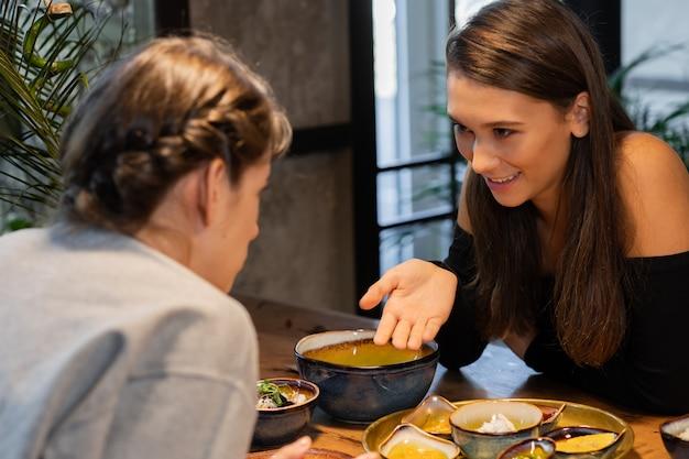 Twee vriendinnen chatten en wat snacks in een cafe