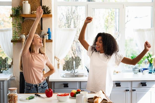 Twee vriendinnen dansen tijdens het koken in de keuken