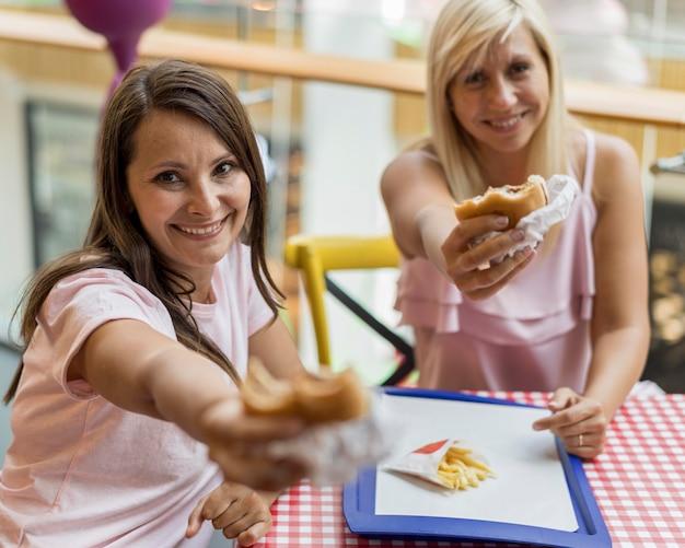 Twee vriendinnen die je hamburgers aanbieden terwijl je in een restaurant bent