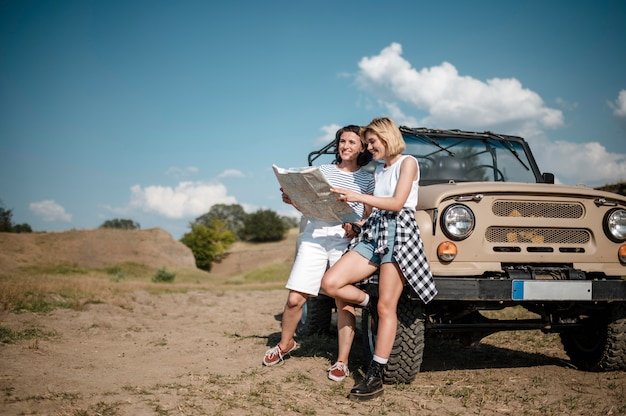 Twee vriendinnen die kaart controleren terwijl ze met de auto reizen