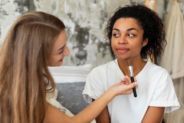 Twee vriendinnen die make-up op elkaar doen
