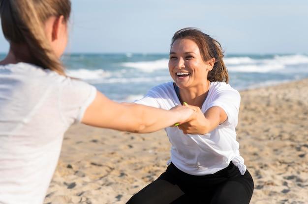 Twee vriendinnen die samen op het strand werken
