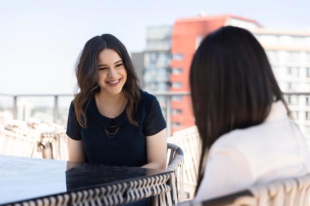 Twee vriendinnen die samen tijd doorbrengen en wijn drinken op een dakterras