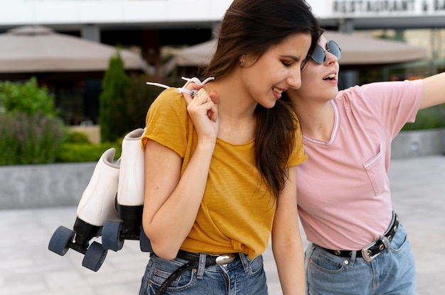 Twee vriendinnen die tijd samen buiten doorbrengen en rolschaatsen dragen