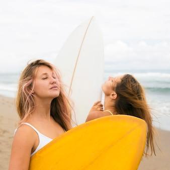 Twee vriendinnen die zich voordeed op het strand met surfplanken