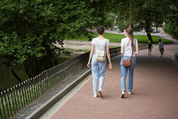 Twee vriendinnen gaan naar het steegje van het park. studenten in de zomer wandelen in het park. achteraanzicht