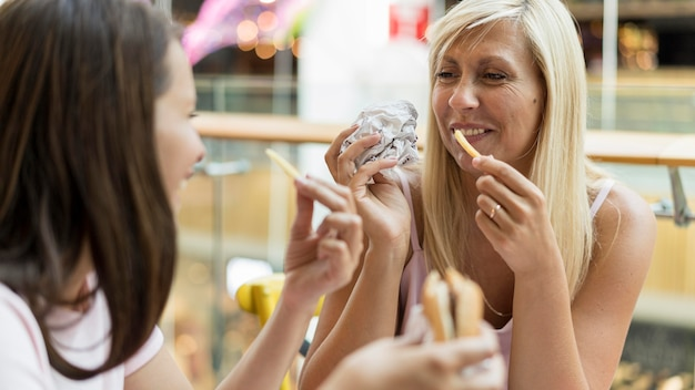 Twee vriendinnen genieten van hamburgers en frietjes in restaurant
