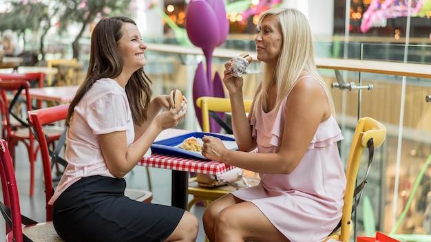 Twee vriendinnen genieten van hamburgers samen in restaurant
