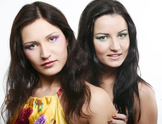 Twee vriendinnen glimlachen samen, studio-opname