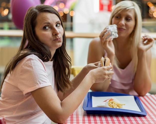 Twee vriendinnen hamburgers eten in restaurant