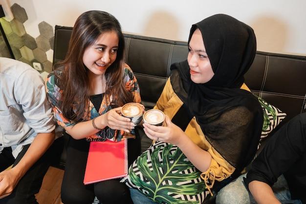 Twee vriendinnen houden een kopje koffie vast wanneer ze samen studeren in een coffeeshop