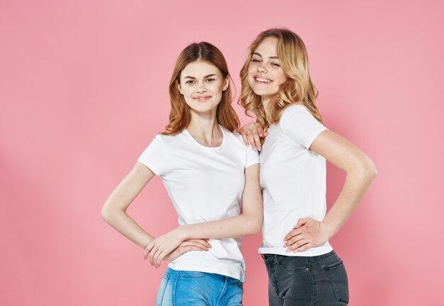 Twee vriendinnen in de witte roze achtergrond van de t-shirtslevensstijl