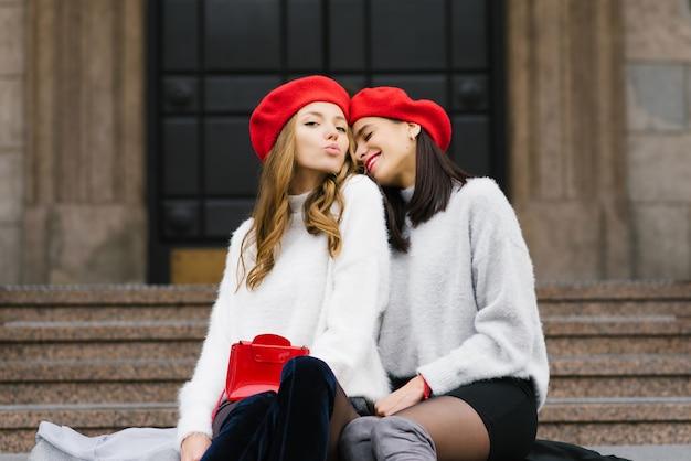 Twee vriendinnen in rode baretten zitten op de trap en glimlachen en blazen een kus. geluk en vreugde in relaties