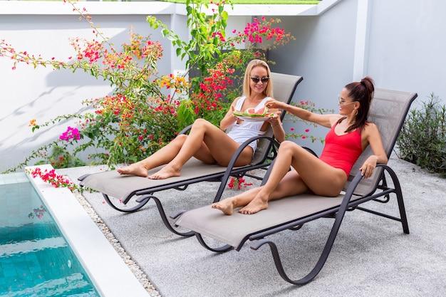 Twee vriendinnen in zwembroek aziatisch en kaukasisch op zonnebank bij zwembad in villa met watermeloen vakantie in tropische landen vers fruit