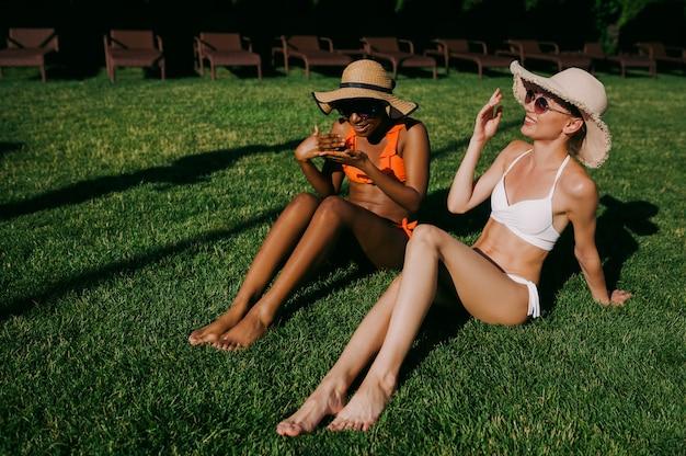 Twee vriendinnen in zwemkleding zonnebaden op gras