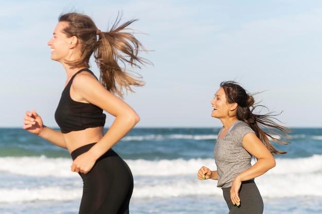 Twee vriendinnen joggen op het strand