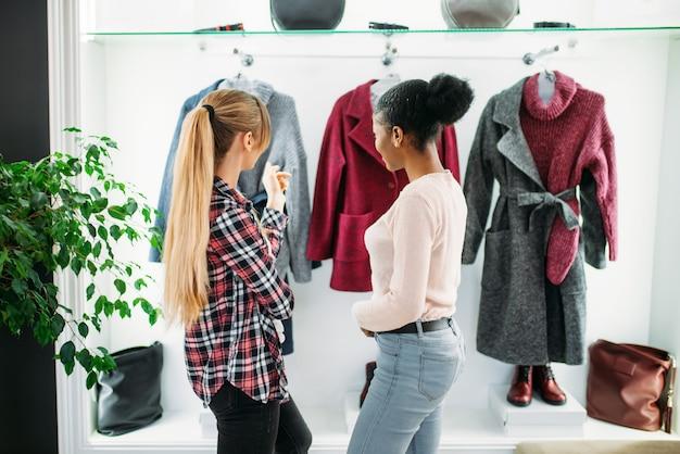 Twee vriendinnen kijken naar de jas in de winkel. shopaholics in kledingwinkel, levensstijl van consumentisme, mode