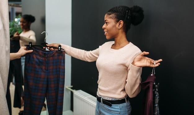 Twee vriendinnen kleren kiezen in de kleedkamer. shopaholics in kledingwinkel, inkoop, mode
