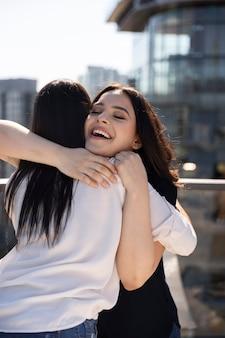 Twee vriendinnen knuffelen nadat ze elkaar op een dakterras hebben gezien