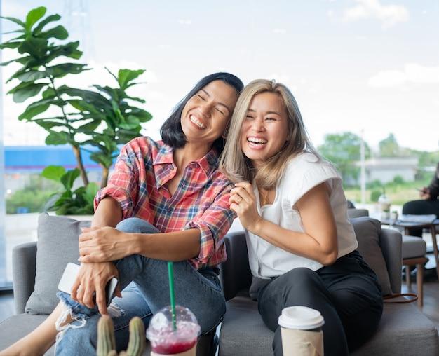Twee vriendinnen lachen om een café.