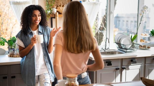 Twee vriendinnen met een gesprek in de keuken