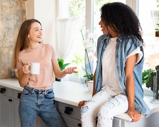 Twee vriendinnen met een gesprek thuis over koffie
