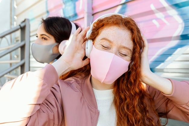 Twee vriendinnen met gezichtsmaskers buiten luisteren naar muziek op de koptelefoon