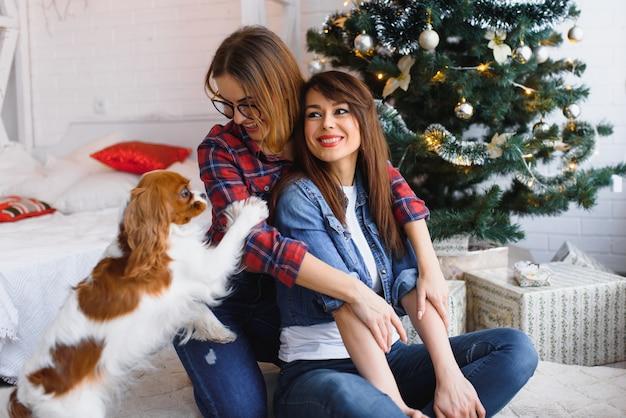 Twee vriendinnen met hond zitten op de vloer lachend in een lichte kamer op de achtergrond van een kerstboom