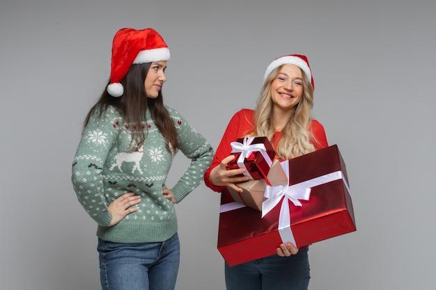 Twee vriendinnen met nieuwjaarsgeschenken op grijze achtergrond met kopieerruimte, alle cadeautjes in één hand
