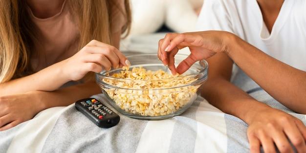 Twee vriendinnen met popcorn in bed terwijl ze tv kijken