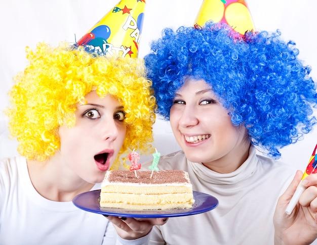 Twee vriendinnen met taart en pruik vieren 21ste verjaardag