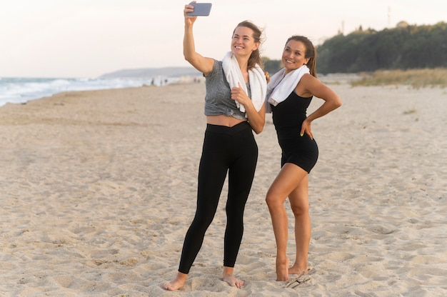 Twee vriendinnen nemen een selfie op het strand tijdens het trainen