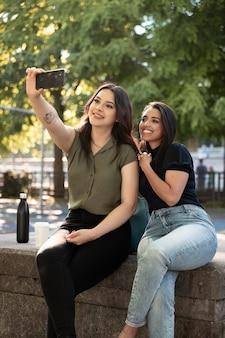 Twee vriendinnen nemen selfie in het park terwijl ze wat koffie drinken